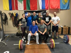 Group of olympic weightlifters posing for a group photo in front of a barbell with flags behind them