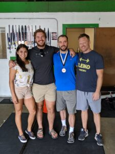 Four people standing in front of a wall of weightlifting medals